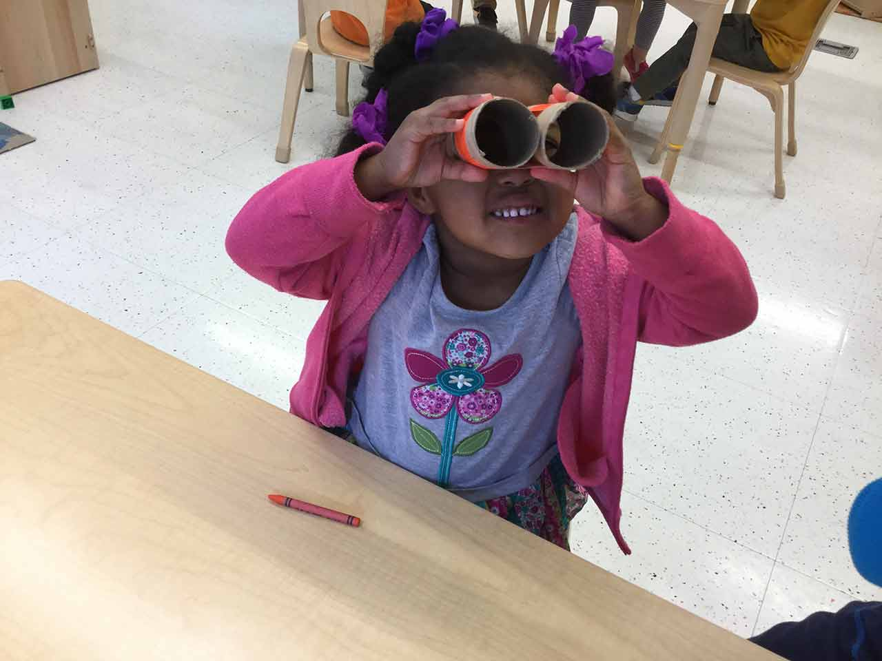 Child looking through a set of binoculars made of paper rolls