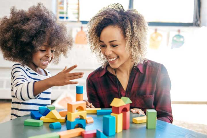 teacher and child playing with colorful blocks and smiling