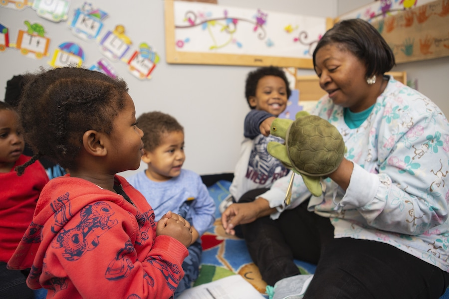 teacher playing with a turtle puppet with students