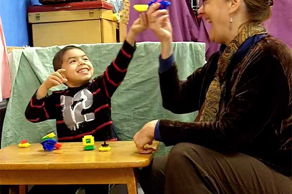 A boy and his teacher playing with toys together
