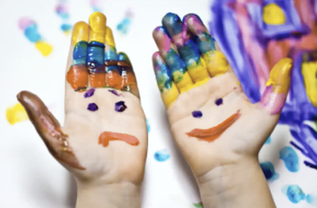 Two young hands with a smiley face and frowny face painted on them