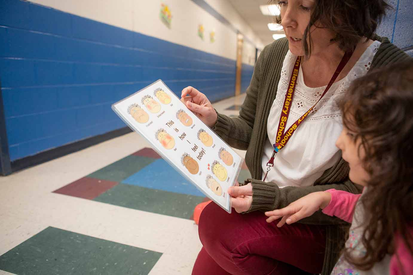 child and teacher looking at emotions chart