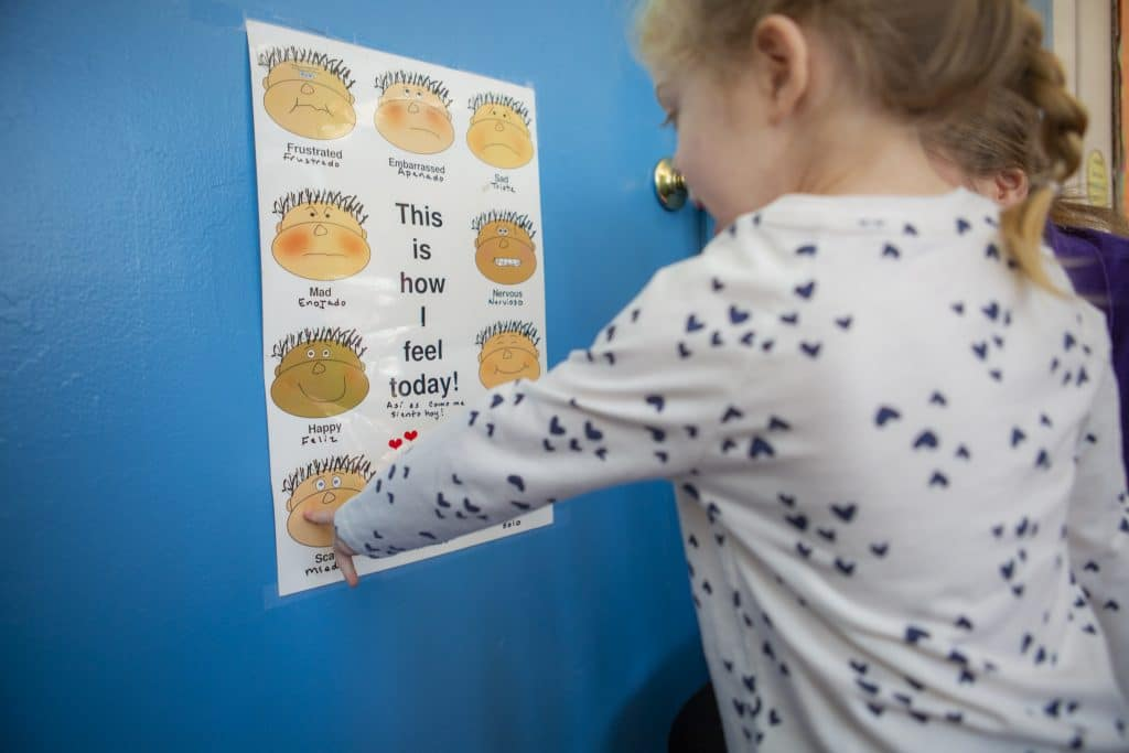 Young girl pointing to emotion chart