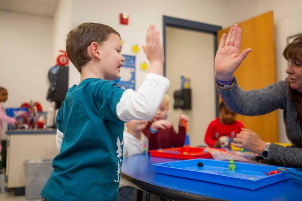 Child and teacher high five and smile
