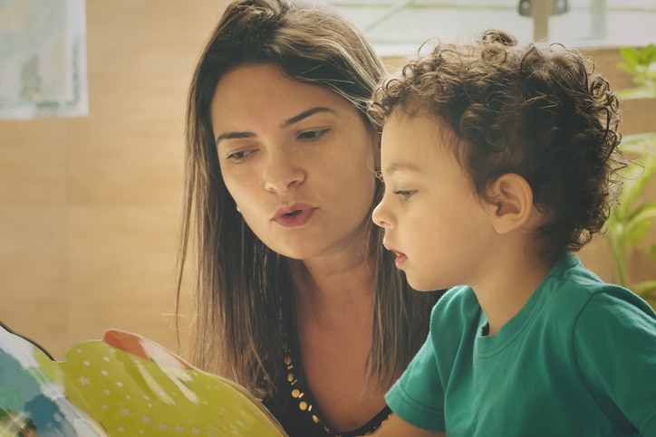 Mother teaching her two years old son with a children's book.