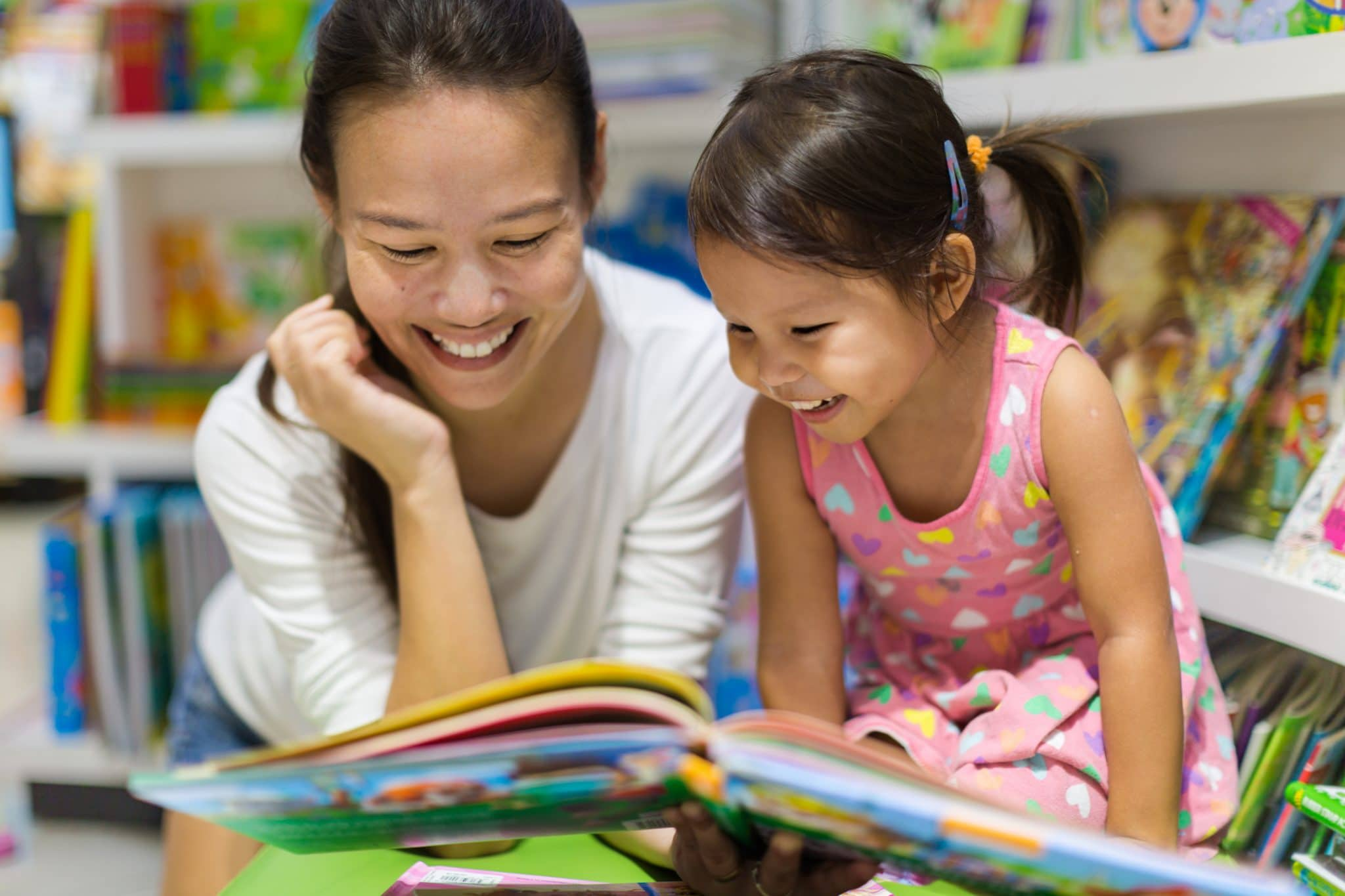 Teacher reading a educational book to her female student, having a good time in class learning.