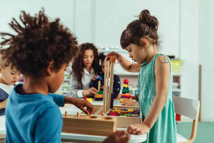 diverse children playing in a classroom center