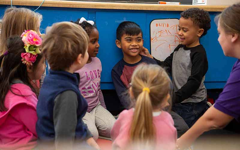 A group of young children in circle time greeting each other