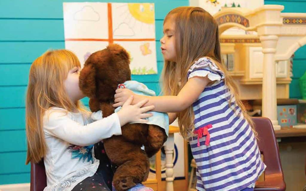 One girl hands a teddy bear to another girl who is seated in a preschool classroom