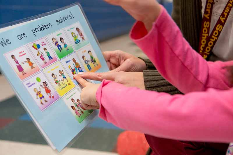 Child pointing at problem solving cards