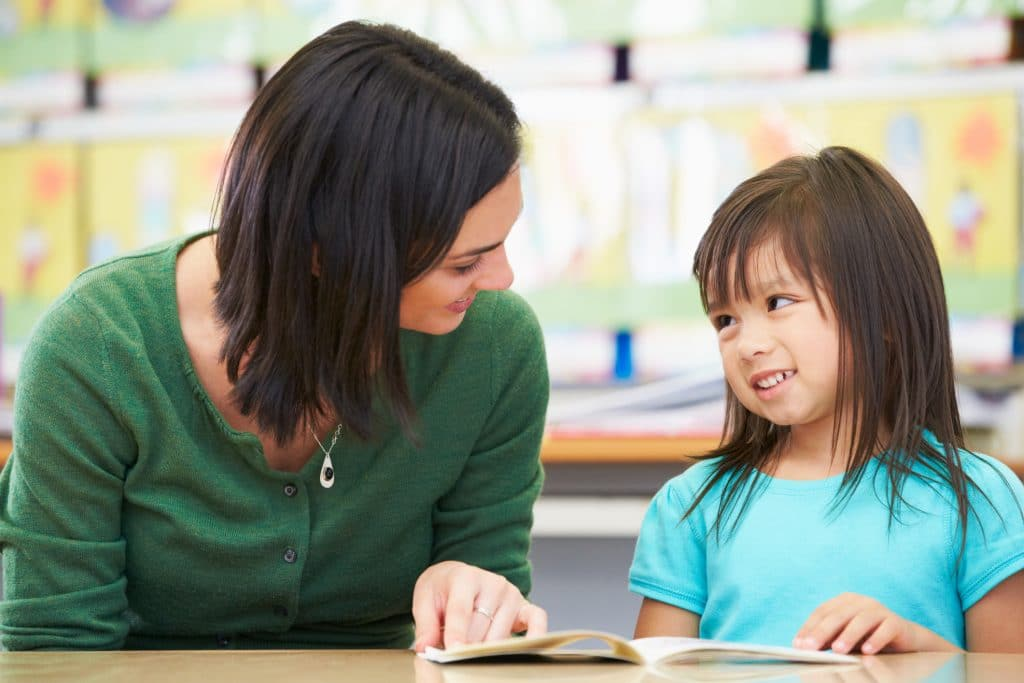 Elementary Pupil Reading With Teacher In Classroom Looking At Each Other Smiling