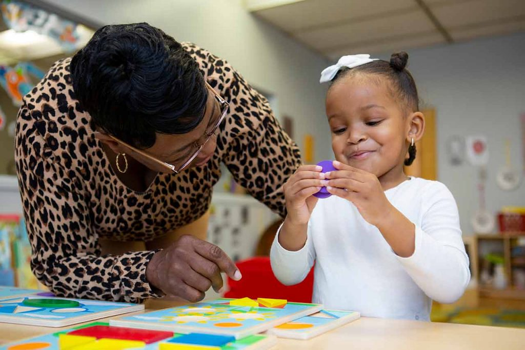Teacher encouraging young child to complete a puzzle