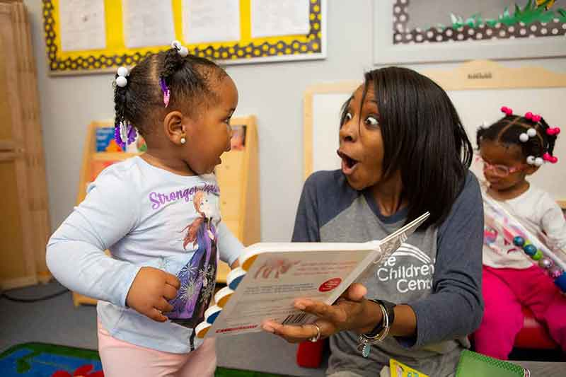 young girl and toddler reading book