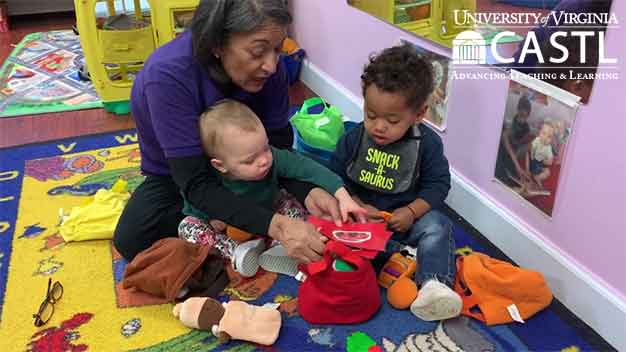 Infant and toddler playing with teacher in a small group